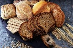 Pão de centeio cortado na placa de corte Pão de centeio da grão e rol inteiros fotografia de stock