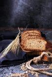 Pão de centeio cortado na placa de corte Pão de centeio inteiro da grão com SE fotografia de stock