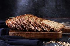 Pão de centeio cortado na placa de corte Pão de centeio inteiro da grão com SE imagens de stock