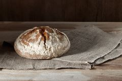 Pão de centeio redondo do trigo no pano de saco em um fundo de madeira Foto de Stock