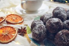 Pão-de-espécie do chocolate, polvilhado com o açúcar pulverizado em uma placa com folhas de turquesa, laranjas secadas, bodyan fotos de stock