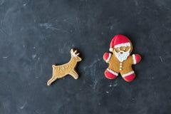 Pão-de-espécie Santa Homens do gengibre com esmalte colorido em um fundo cinzento Fotografia de Stock