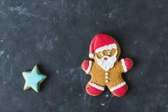 Pão-de-espécie Santa Homens do gengibre com esmalte colorido em um fundo cinzento Foto de Stock