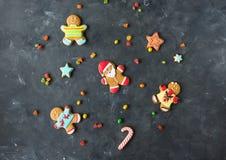 Pão-de-espécie Santa Homens do gengibre com esmalte colorido em um fundo cinzento Fotos de Stock