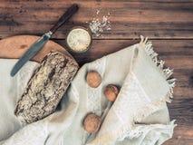 Pão de mistura com a crosta rachada envolvida em um pano de uma tela áspera Ainda vida do sal, das nozes, da faca e do pano sobre Fotos de Stock