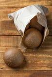 Pão de Rye no saco de papel no fundo de madeira Fotografia de Stock Royalty Free