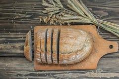 Pão de uma mistura da farinha cortada em um fundo de madeira fotografia de stock royalty free