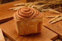 Pão delicioso, bonito, caseiro em um fundo de madeira em um estilo rústico Pão recentemente cozido em uma placa de madeira Rústic Imagens de Stock