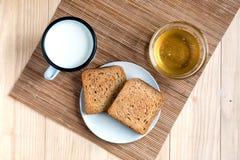 Pão do brinde com Tin Mug do leite e do frasco do mel fotos de stock royalty free