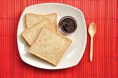 Pão do Wholewheat com atolamento no fundo vermelho Fotografia de Stock