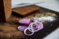 Pão e cebolas em um sal da placa de corte Fotos de Stock