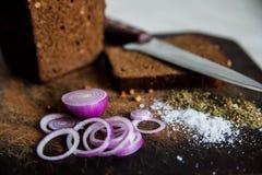 Pão e cebolas em um sal da placa de corte Fotografia de Stock Royalty Free