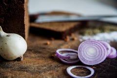 Pão e cebolas em um sal da placa de corte Imagens de Stock