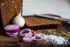 Pão e cebolas em um sal da placa de corte Imagens de Stock Royalty Free