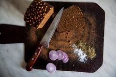 Pão e cebolas em um sal da placa de corte Fotos de Stock Royalty Free