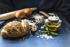 Pão e ingredientes cortados nas ardósias do preto, fim do pão acima fotografia de stock royalty free