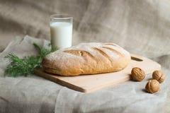 Pão e leite com nozes e aneto em uma placa de madeira foto de stock royalty free