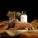 Pão e leite em uma tabela em uma tela áspera, estilo rústico Fotografia de Stock
