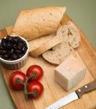 Pão e queijo/queijo de creme orgânico delicioso do leite, azeitonas e tomates casa-feitos do pão e os maduros na placa de madeira Imagem de Stock Royalty Free