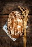 Pão e trigo rústicos na tabela da madeira do vintage Fotos de Stock