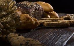 Pão e trigo rurais em uma tabela de madeira antiga velha, ainda vida Foto de Stock Royalty Free