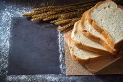 Pão em uma placa de corte de madeira e as grões do trigo colocadas ao lado com quadro do espaço da cópia foto de stock