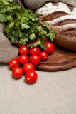 Pão em uma placa de madeira com tomates Imagem de Stock