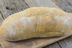 Pão em uma placa de pão com madeira rústica Fotografia de Stock Royalty Free