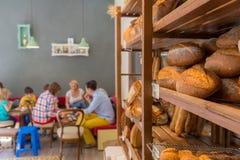 Pão em uma prateleira com os povos que sentam-se em tabelas Fotografia de Stock Royalty Free