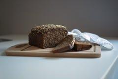 Pão escuro com as sementes na tabela branca imagens de stock royalty free