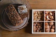 Pão escuro com sementes de girassol, diversos tipos das porcas em uma caixa, conceito do cereal de comer saudável, em um fundo de Imagens de Stock Royalty Free