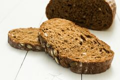 Pão escuro da rua com sementes em um fundo branco foto de stock