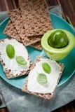 Pão estaladiço com queijo creme e as ervas frescas em uma placa de madeira fotos de stock royalty free