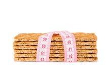 Pão estaladiço da dieta e fita de medição isolados imagens de stock