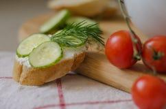 Pão francês com queijo, os pepinos e aneto cremosos na parte superior Fotos de Stock Royalty Free