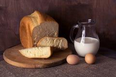 Pão fresco caseiro, leite em um jarro e ovos em uma tabela de madeira Imagens de Stock