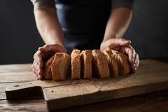 Pão fresco da casa da fatia nas mãos masculinas do ` s na tabela de madeira imagens de stock royalty free