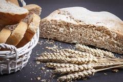 Pão fresco, fatias de pão cortado na cesta e orelhas do trigo no fundo preto Pão e migalhas na tabela Padaria rural foto de stock royalty free