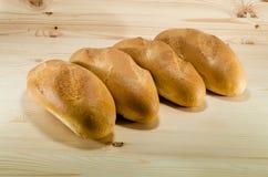 Pão fresco no fundo de madeira da tabela Conceito da padaria grupo dos loafs que colocam na linha Fotografia de Stock