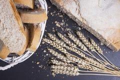 Pão fresco, spikelets do trigo e pão cortado em um fundo cerâmico preto Padaria rural fotografia de stock