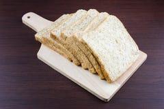 Pão integral inteiro cortado em desbastar a madeira Imagem de Stock