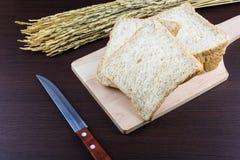 Pão integral inteiro cortado em desbastar o backg de madeira e tricotado manualmente Fotos de Stock