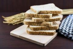Pão integral inteiro cortado em desbastar o backgro da madeira e da toalha de mesa Imagem de Stock Royalty Free