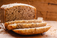 Pão integral inteiro cortado na placa de corte Fotos de Stock