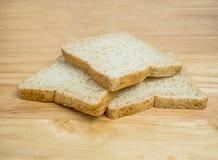 Pão integral inteiro de três fatias empilhado na tabela Fotografia de Stock Royalty Free