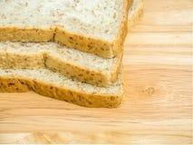 Pão integral inteiro de três fatias na tabela de madeira Fotografia de Stock