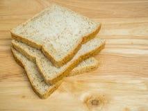Pão integral inteiro de três fatias na tabela de madeira Fotografia de Stock Royalty Free