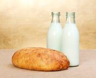 Pão inteiro e dois frascos de leite Imagens de Stock Royalty Free