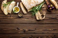 Pão italiano caseiro delicioso do ciabatta com azeite e azeitonas no fundo rústico de madeira, acima da vista, espaço para o text imagem de stock royalty free