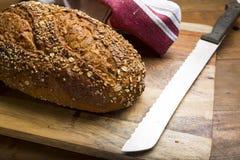 Pão no close up da placa de corte e da faca de pão Fotos de Stock Royalty Free